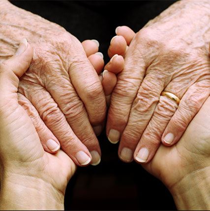An Elderly person and a young person holding hands